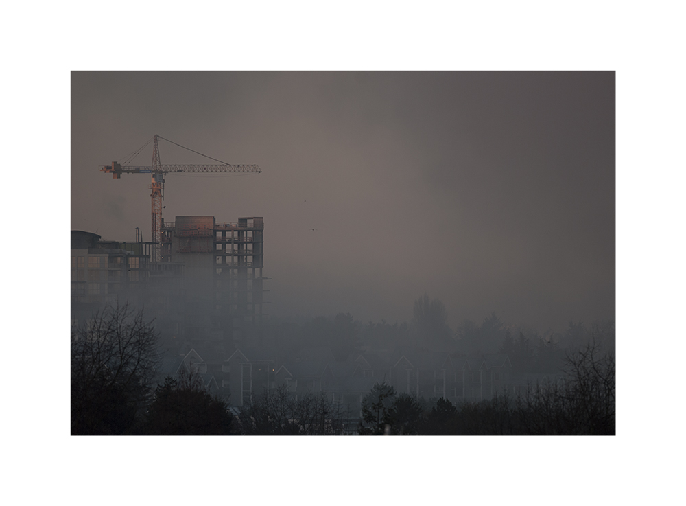 A crane rises above the fog.  That crane's been there for ages.  Will that building ever be finished?